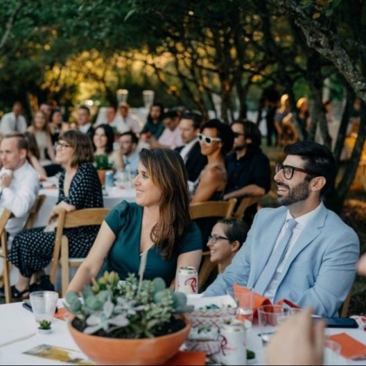 Guests seated at an outdoor reception inside under the trees of Goodfellow Grove