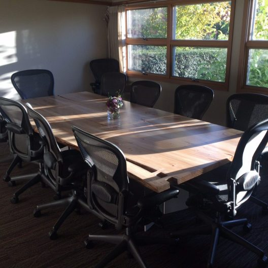 Small boardroom with seating for 8 surrounding a large ash wood table