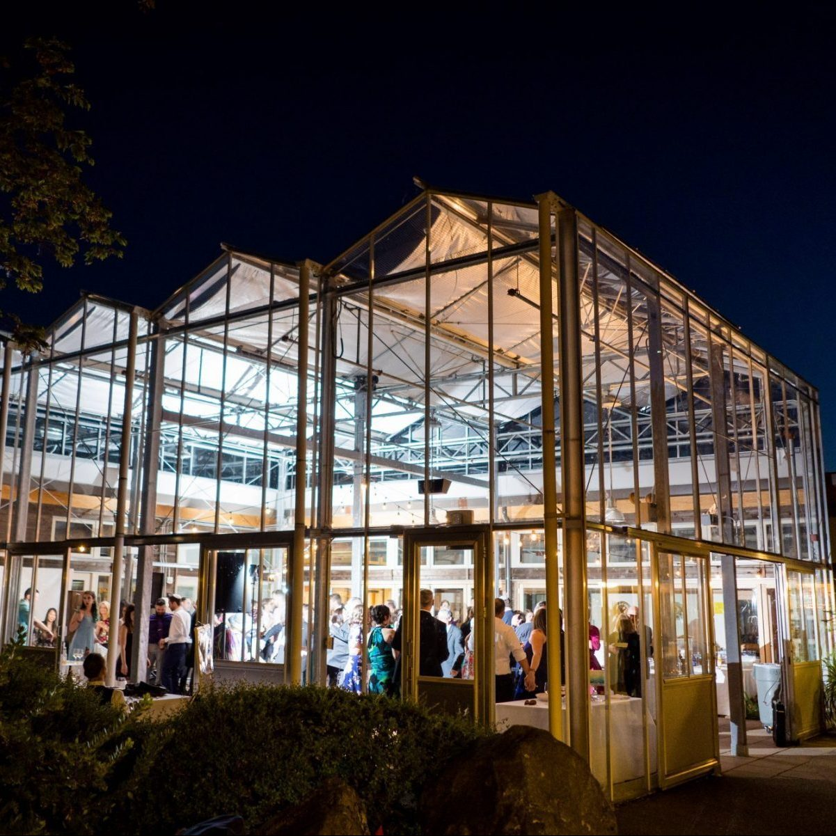 An all glass atrium lit up at night with guests mingling inside